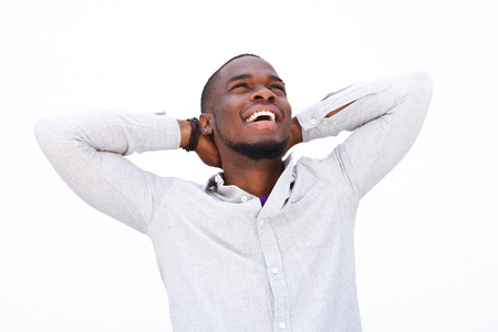 hands on head: Portrait of a smiling black man relaxing and smiling with hands behind head on white background Stock Photo