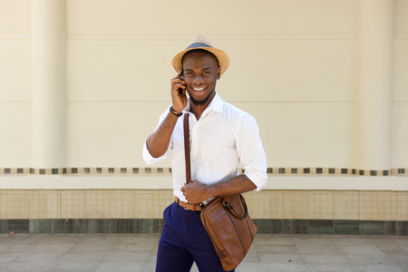 sidewalk talk: Portrait of a handsome young guy talking on mobile phone