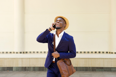 Portrait of a cool young african man in suit and hat walking and talking on mobile phone