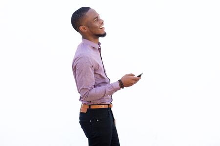 Seitenporträt eines netten afrikanischen Mannes mit Handy und lachend gegen weißen Hintergrund