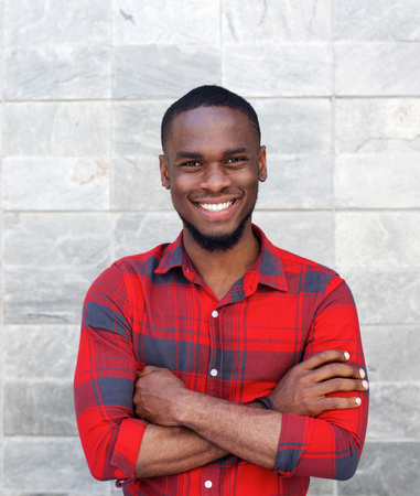 posing: Portrait of a happy young black guy smiling with arms crossed while standing against gray wall