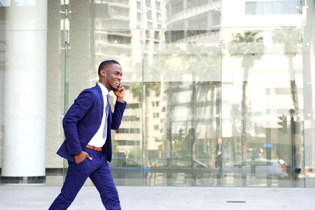Side portrait of a happy young man in suit walking and talking on mobile phone