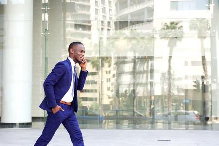 Zij portret van een gelukkige jonge man in pak lopen en praten over de mobiele telefoon