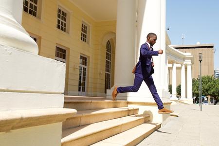 hombres jovenes: retrato de cuerpo entero del hombre de negocios corriendo de un edificio en la ciudad