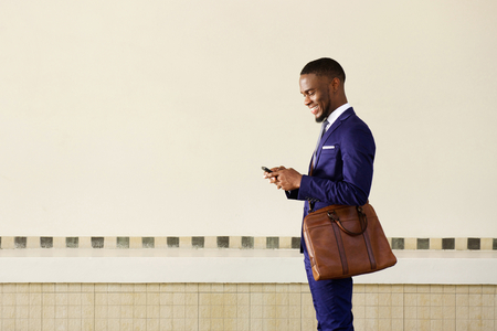 mobile app: Side portrait of a happy young businessman with bag  reading text message on mobile phone Stock Photo