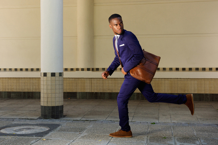 african business: Full length portrait of young businessman running and looking over shoulder
