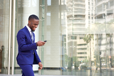 Side portrait of a happy young man in suit walking and reading text message on his mobile phone Foto de archivo