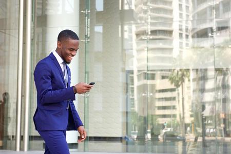 Zij portret van een gelukkige jonge man in pak lopen en het lezen van SMS-bericht op zijn mobiele telefoon