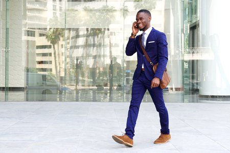 Full length portrait of a confident young businessman walking in the city talking on cell phone Standard-Bild