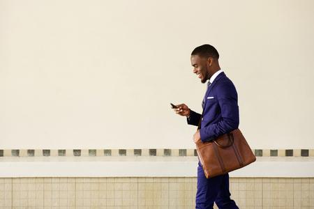 Retrato lateral de un hombre de negocios sonriente con la bolsa de caminar al aire libre