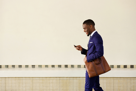 Ritratto laterale di un uomo d'affari sorridente con il sacchetto camminare all'aperto