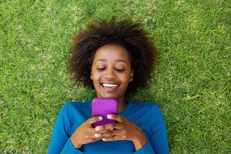Portrait de dessus d'une femme africaine souriante allongé sur l'herbe en regardant téléphone cellulaire