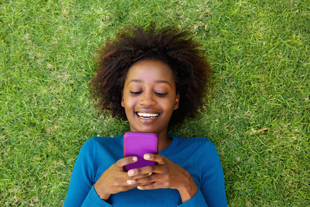 looking at: Portrait from above of a smiling african woman lying on grass looking at cell phone