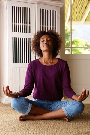 practising: Portrait of an african american woman practising yoga at home Stock Photo