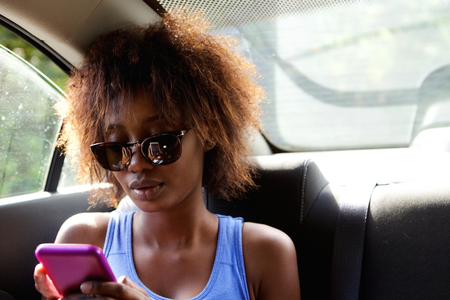 looking at: Close up portrait of a young african american woman sitting n backseat of car looking at cell phone Stock Photo