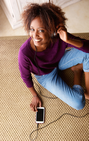 women sitting: Portrait of a black woman smiling with smart phone and headphones
