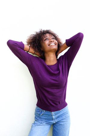 woman hands up: Portrait of a smiling african american woman with hands behind head and looking up