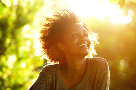 일몰과 함께 웃는 아름다운 아프리카 계 미국인 여자의 초상화를 닫습니다