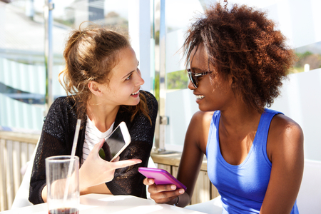 two: Close up portrait of two friends sitting at restaurant with mobile phone Stock Photo