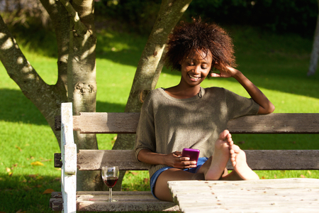 Portrait of a smiling black woman sitting in park with mobile phone Stock Photo
