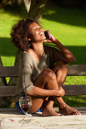 woman barefoot: Portrait of a happy black woman sitting outside with mobile phone