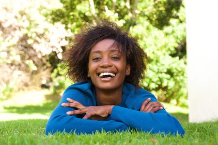 ser humano: Retrato de una mujer joven y atractiva negro tumbado en la hierba de risa Foto de archivo