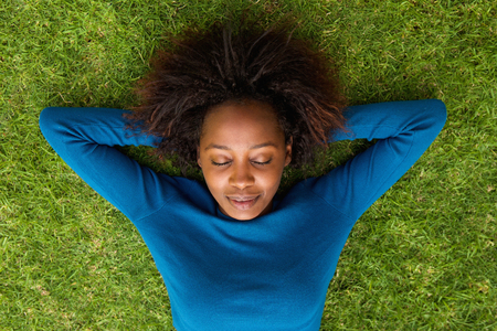Portrait from above of a young african woman lying on grass sleeping Foto de archivo