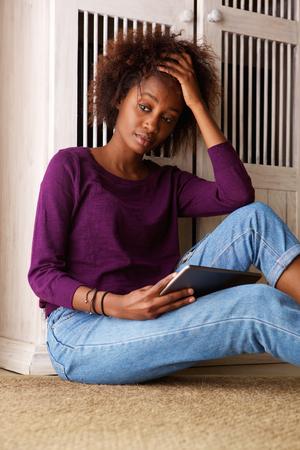 women sitting: Portrait of a black woman sitting with digital tablet