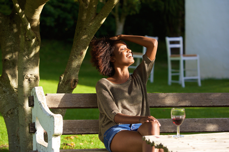 negras africanas: Portrait of a smiling african woman relaxing outside in garden