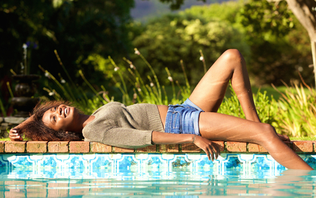 Portrait of a smiling young woman lying by pool
