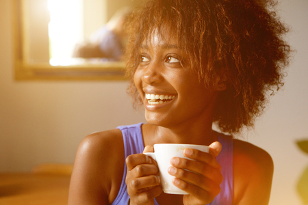 laughing face: Close up portrait of a smiling young african american woman with coffee cup Stock Photo