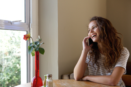 relaxing at home: Portrait of a smiling young woman talking with mobile phone at cafe