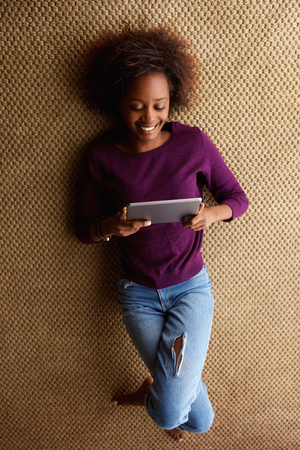 women sitting: Portrait from above young black woman lying down with digital tablet