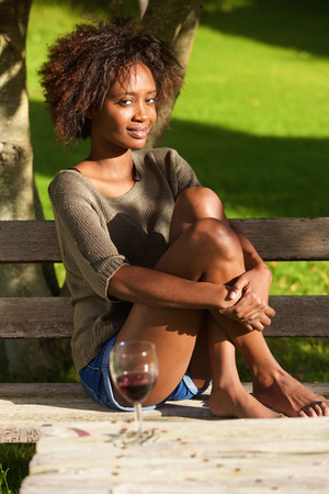 negras africanas: Portrait of a young african american woman sitting barefoot in park