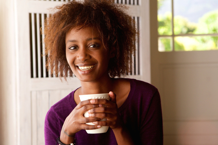 people laughing: Close up portrait of a smiling young african american woman drinking coffee Stock Photo