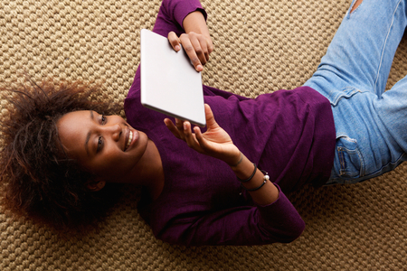 woman laying: Portrait from above smiling black woman lying down with digital tablet