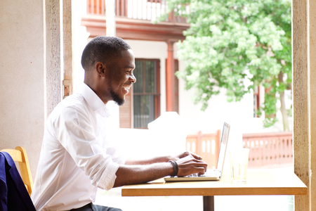 working desk: Side portrait of a handsome african businessman smiling with laptop at cafe Stock Photo