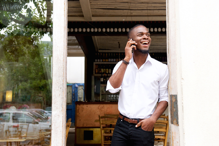 american: Portrait of a smiling young black businessman talking on mobile phone