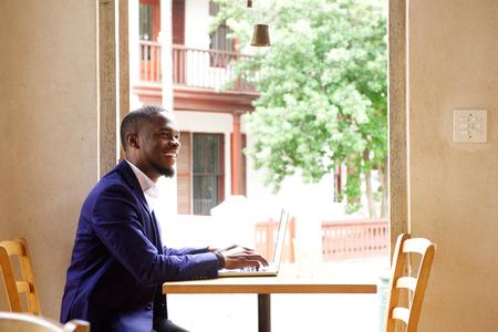 black businessman: Side portrait of a handsome black businessman smiling with laptop at cafe