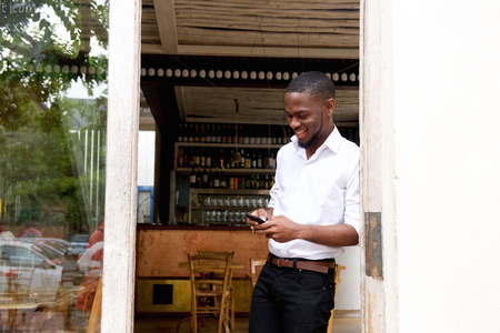 mobile app: Portrait of a smiling businessman looking at mobile phone