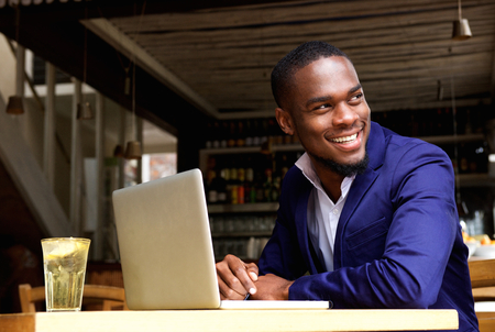 confianza: Retrato de un hombre de negocios negro sonriente con la computadora portátil en el café
