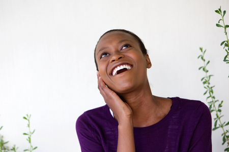 carefree: Close up portrait of smiling young african woman looking away