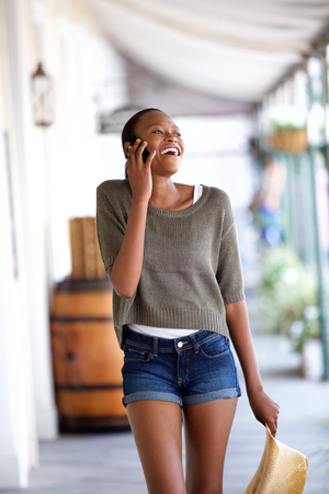 smiling girl: Portrait of happy young african woman walking and talking on mobile phone