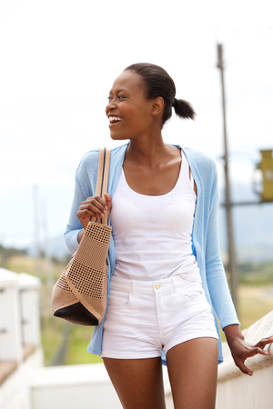 lady hand: Portrait of happy young african lady walking outdoors and  looking away