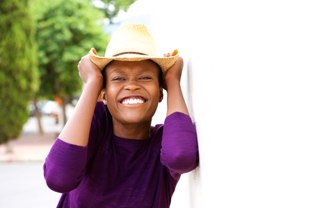 casual: Close up portrait of young african woman wearing a hat looking excited