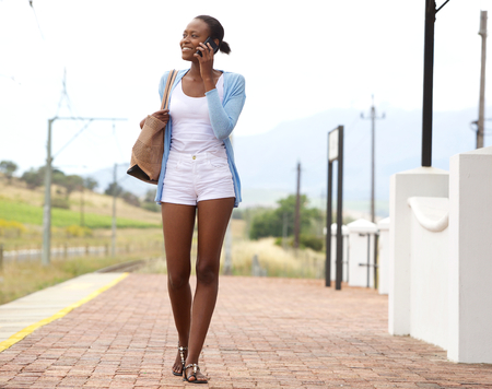 phone call: Full length portrait of young african woman at railway station making a phone call Stock Photo