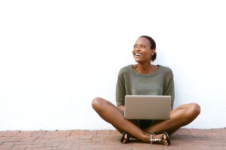 outside: Portrait of happy young african american woman sitting on sidewalk with laptop