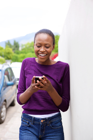 happy african: Portrait of happy young african woman leaning against wall looking at cell phone