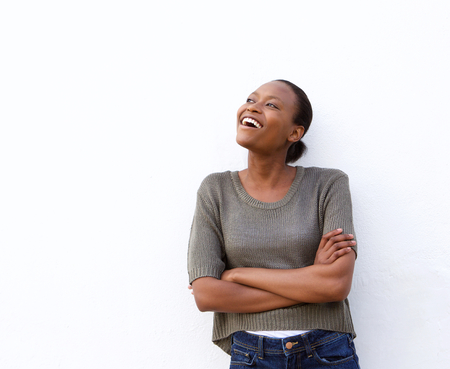 niña pensando: Portrait of laughing young african woman standing against white background and looking away Foto de archivo