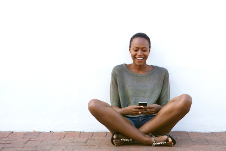 hone: Portrait of happy young woman sitting on sidewalk with cell hone